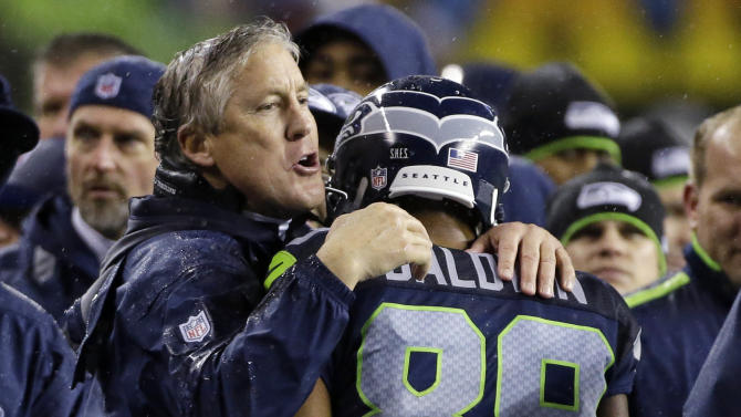 Seattle Seahawks' head coach Pete Carroll, left, hugs Doug Baldwin after Baldwin scored a touchdown against the San Francisco 49ers in the second half of an NFL football game, Sunday, Dec. 23, 2012, in Seattle. (AP Photo/Elaine Thompson)