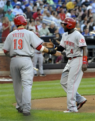 Cincinnati Reds' Brandon Phillips (4) is greeted at home plate by Joey Votto (19) after they both scored on a fielding error by New York Mets third baseman David Wright in the first inning of a baseba