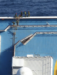 Italian firefighters work on the grounded cruise ship Costa Concordia off the Tuscan island of Giglio, Italy, Monday, Jan. 30, 2012. Residents of Giglio are growing increasingly worried about threats to the environment and the future of the Italian island as bad weather again forced suspension of the recovery operation of the capsized cruise ship Costa Concordia. (AP Photo/Pier Paolo Cito)