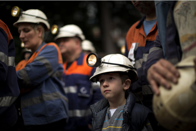 A boy wears the helmet of his father as coal miners attend a speech of one of their leaders during a protest march in Langreo near Oviedo, Spain, Monday, June 18, 2012.  Unions for Spanish coal mining