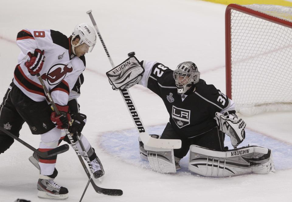 Los Angeles Kings goalie Jonathan Quick (32) deflects a shot attempt as New Jersey Devils right wing Dainius Zubrus (8) looks for the rebound in the first period during Game 3 of the Stanley Cup Finals, Monday, June 4, 2012, in Los Angeles.  (AP Photo/Jae C. Hong)
