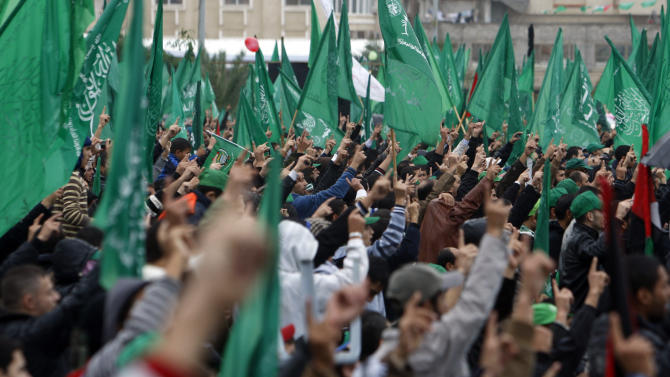 Palestinian Hamas activists raise their fingers while chanting Islamic slogans as other wave green Islamic flags during a rally to commemorate the 25th anniversary of the Hamas militant group, in Gaza city, Saturday, Dec. 8, 2012.  Hamas chief Khaled Mashaal is expected to speak at Saturday's rally in Gaza City after entering the seaside strip a day earlier after a long exile from Palestinian territory. (AP Photo/Adel Hana)