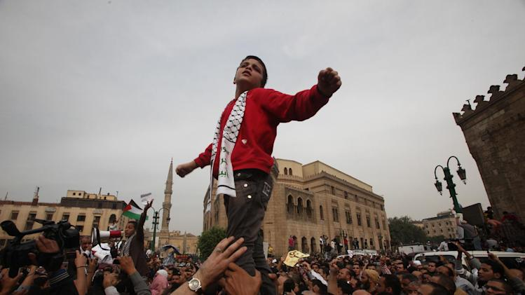 An Egyptian boy leads protesters in chanting slogans against the Israeli invasion of Gaza, outside Al-Azhar mosque where President Mohammed Morsi's Muslim Brotherhood called for demonstrations after Friday prayers, in Cairo, Egypt, Friday, Nov. 16, 2012. In his Friday sermon in Al-Azhar, influential cleric Sheikh Yusuf al-Qaradawi, not shown, said the Islamic world would not be silent in the face of Israel's military operation in Gaza. (AP Photo/Thomas Hartwell)