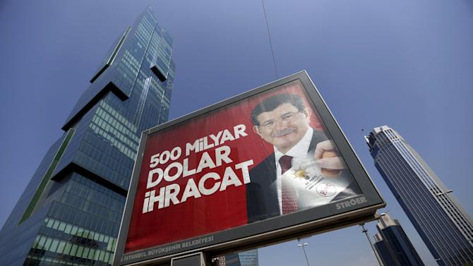 """An election billboard with a picture of Turkish Prime Minister Davutoglu and a slogan reads that: """"500 Billion Dollars Export"""" is pictured in Istanbul's financial district of Levent, Turkey"""