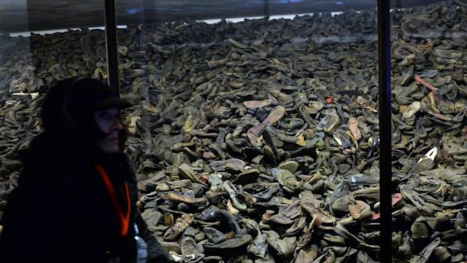 A visitor walks past prisoners' shoes on display at the memorial site of the former Auschwitz concentration camp in Oswiecim, Poland on January 26, 2015
