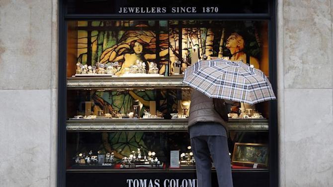 A woman looks at jewellery in a shop window in central Barcelona