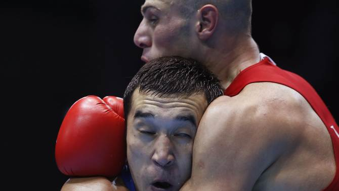 Iran's Ehsan Rouzbahani fights with Kazakhstan's Adilbek Niyazymbetov  during their men's light heavy (81kg) semi-final boxing match at the Seonhak Gymnasium during the 2014 Asian Games in Incheon