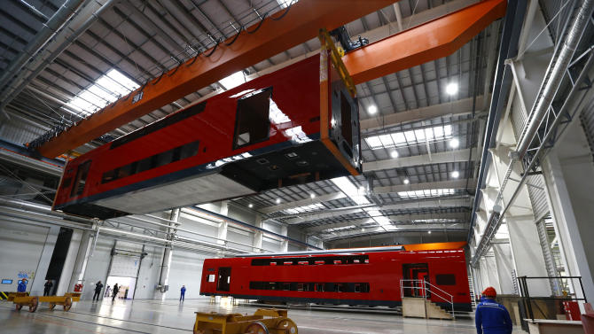 """Employees work on an electric train assembly line at the """"Stadler Minsk"""" plant in Fanipol"""