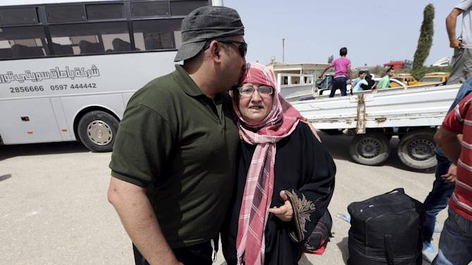 A Palestinian man kisses his mother on the head upon her return to Gaza at the Rafah border crossing between Egypt and southern Gaza Strip