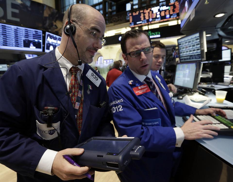 Trader Luigi Muccitelli, left, and specialist Michael Pistillo, center, work on the floor of the New York Stock Exchange Monday, April 29, 2013.  A pair of encouraging economic reports helped propel the stock market up in early trading on Monday. (AP Photo/Richard Drew)