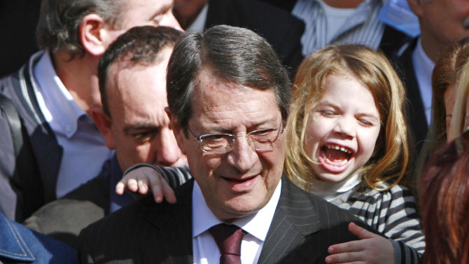 Right-wing opposition leader and presidential candidate Nicos Anastasiades with his granddaughter Nikoletta leaves after voting in the presidential election in southern port city of Limassol, Cyprus, Sunday, Feb. 24, 2013. Anastasiades garnered 45.46 per cent of the vote in the first round of voting, some 18 points over communist-backed Stavros Malas. (AP Photo/Petros Karadjias)