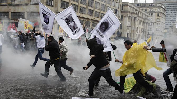 Protesters run through a flooded street from tear gas fired by police after a May Day march ended in clashes in downtown Bogota, Colombia, Tuesday, May 1, 2012. (AP Photo/Fernando Vergara)