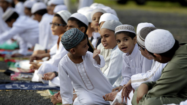 Muslims children attend Eid al-Fitr prayer, which marks the end of the holy month of Ramadan in Panama City, Sunday, Aug. 19, 2012. Muslims around the world celebrate Eid al-Fitr, marking the end of Ramadan, the Muslim calendar's ninth and holiest month. According to the International Journal of Environmental Science and Development, around 10.000 Muslims reside in Panama. (AP Photo/Arnulfo Franco)