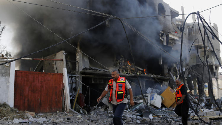 Palestinian firefighters inspects the damage of a destroyed milk factory after it was hit by an Israeli airstrike in Gaza City, Thursday, July 31, 2014. Israel said Thursday it has called up another 16,000 reservists, allowing it to potentially widen its Gaza operation against the territory's Hamas rulers in a three-week-old war that has killed more than 1,300 Palestinians and more than 50 Israelis. (AP Photo/Hatem Moussa)