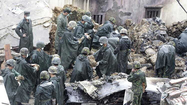 Soldiers clean up wreckage of a TransAsia Airways turboprop plane that crashed, on Taiwan's offshore island Penghu