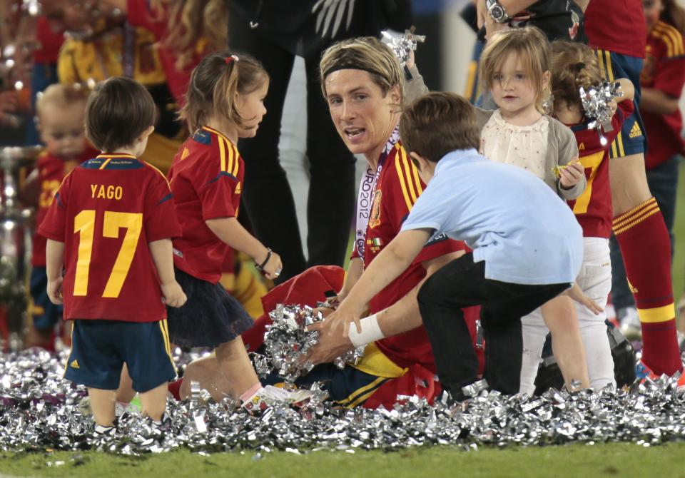 Children brought onto the pitch by celebrating Spanish surround Spain's Fernando Torres during the Euro 2012 soccer championship final  between Spain and Italy in Kiev, Ukraine, Monday, July 2, 2012. (AP Photo/Ivan Sekretarev)  (AP Photo/Ivan Sekretarev)