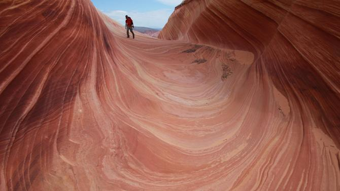 FILE-This May 28, 2013 file photo shows a on a rock formation known as The Wave in the Vermilion Cliffs National Monument in Arizona. Authorities say a California couple is dead after hiking this southern Utah trail in temperatures higher than 100 degrees. Kane County deputies say 70-year-old Ulrich Wahli and his 69-year-old wife Patricia Wahli were found dead Thursday July 4, 2013, morning in this popular hiking area called The Wave. (AP Photo/Brian Witte,File)