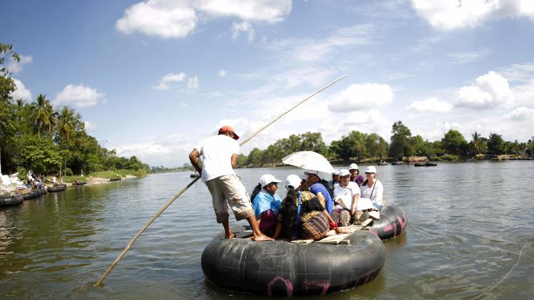 "Women from ""Caravana de Madres Centroamericanas"" ride a raft to cross to Guatemala from the Suchiate river in the border of Ciudad Hidalgo"