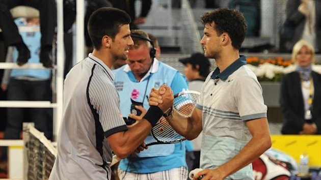 Serbian player Novak Djokovic (L) shakes hands with Bulgarian player Grigor Dimitrov at the end of their tennis match at the Madrid Masters