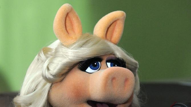 """FILE -In this Nov. 12, 2011 file photo, Miss Piggy arrives at the premiere of  The Muppets at the El Capitan Theater, in Los Angeles. Kermit the Frog, Miss Piggy, Bert and Ernie of """"Sesame Street"""" fame, the stars of """"Fraggle Rock"""" and other puppets, costumes and items from throughout Muppets creator Jim Henson's career have been donated to the Museum of the Moving Image, which is building a new gallery to house them, the institution announced Tuesday, May 21, 2013. (AP Photo/Katy Winn, File)"""