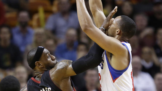 Miami Heat's LeBron James (6)  defends against Philadelphia 76ers' Evan Turner (12) during the first half of a NBA basketball game in Miami, Friday, March 8, 2013. (AP Photo/J Pat Carter)