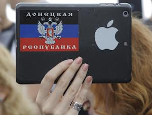 A woman takes pictures of pro-Russian fighters on an…