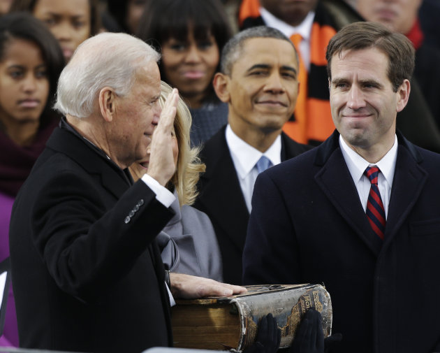 President Barack Obama, center and Beau Biden, Attorney of Deleware, right, watch as his father Joe Biden is sworn in at the ceremonial swearing-in at the U.S. Capitol during the 57th Presidential Ina