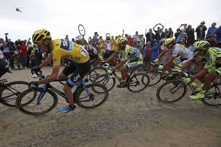 Team Sky rider Froome of Britain, race leader and yellow jersey holder, and Tinkoff-Saxo rider Alberto Contador of Spain cycle on a cobble-stoned section during the 4th stage of the 102nd Tour de France cycling race from Seraing in Belgium to Cambrai