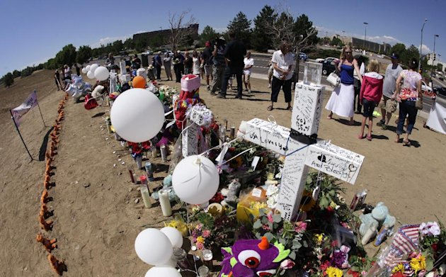 In this photo made with a fish-eye wide-angle lens, visitors view the growing memorial to the victims of last Friday's mass shooting in a movie theater in Aurora, Colo., including a cross dedicated to Matt McQuinn, at right, Tuesday, July 24, 2012. Throughout the day people continued to bring flowers, candles, and other items to the memorial, which is located across the street from the theater. Police have identified the suspected shooter as James Holmes, 24. (AP Photo/Ted S. Warren)