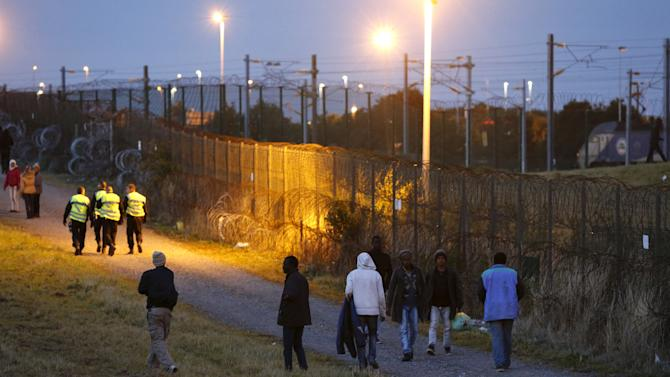 Migrants walk past a fence as another one tries to go in Eurotunnel freight shuttle near the Channel Tunnel access in Coquelles, near Calais