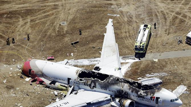 FILE - This Saturday, July 6, 2013 aerial file photo shows the wreckage of the Asiana Flight 214 airplane after it crashed at the San Francisco International Airport in San Francisco. Officials are looking into whether some attorneys may have violated a U.S. law barring uninvited solicitation of air disaster victims in the first 45 days after an accident in connection with the crash landing of Asiana Flight 214 in San Francisco. The National Transportation Safety Board says it has received an unspecified number of complaints about solicitations since the July 6 accident that killed three Chinese teenage girls and injured 180. (AP Photo/Marcio Jose Sanchez)