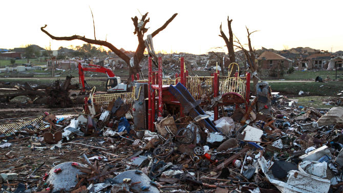 The wreckage of homes litters a playground adjacent to a neighborhood which was destroyed Monday when a tornado moved through Moore, Okla., Wednesday, May 22, 2013. The huge tornado roared through the Oklahoma City suburb, flattening a wide swath of homes and businesses. (AP Photo/Brennan Linsley)