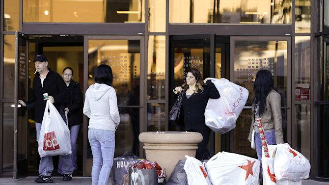 Daisy Marques, far right, and her sister, Daisy Marquez, second from left, stand outside a J.C. Penney store as they wait for their father to bring the car around to load their packages Friday, Nov. 23, 2012, in Las Vegas. Black Friday, the day when retailers traditionally turn a profit for the year, got a jump start this year as many stores opened just as families were finishing up Thanksgiving dinner. (AP Photo/Julie Jacobson)