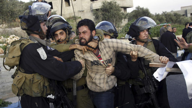 Israeli security forces detain a Palestinian during clashes in the West Bank village of Anin, Saturday, Jan. 26, 2013. Hundreds of Palestinians clashed with Israeli security during a rally in support of Palestinians in Israeli jails. (AP Photo/Mohammed Ballas)