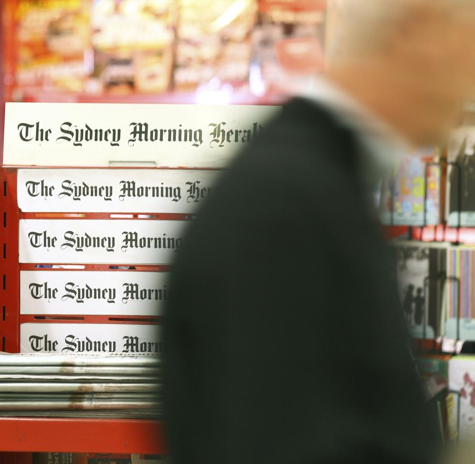 A man walks past a newspaper stand offering the Sydney Morning Herald newspaper in Sydney, Monday, June 18, 2012. Australian publisher Fairfax Media Ltd. said Monday it will shed 1,900 jobs over three years and erect pay walls for two flagship newspapers as readers increasingly move online. (AP Photo/Rick Rycroft)