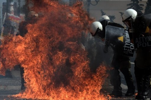 <p>A firebomb explodes near riot police during clashes with demonstrators during a 24-hour strike in Athens on October 18. One man died Thursday at an anti-austerity rally in Athens held during a national general strike as EU leaders were to tackle the eurozone crisis at a summit in Brussels.</p>