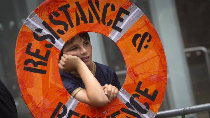 "A child rests on the sideline at the midway point of the ""People's Climate March"" down 6th Ave. in the Manhattan borough of New York"