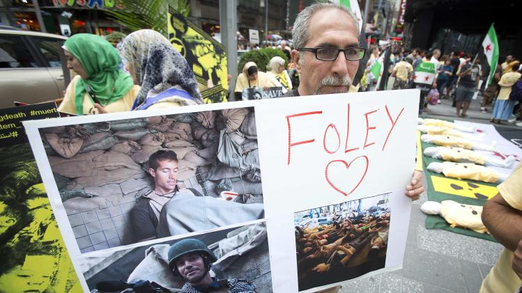 A man holds up a sign supporting American journalist James Foley during a protest against the Assad regime in Syria in Times Square in New York