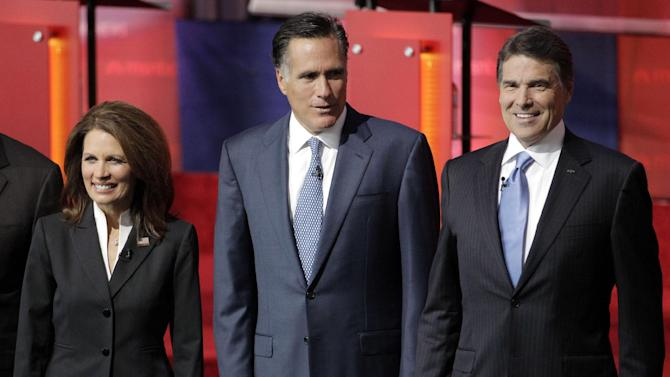 """FILE - In this Sept. 7, 2011, file photo, Republican presidential candidates, from left, Rep. Michele Bachmann, R-Minn., former Massachusetts Gov. Mitt Romney, and Texas Gov. Rick Perry, stand together before a Republican presidential candidate debate at the Reagan Library in Simi Valley, Calif. It's easy to forget there was a time when  Bachmann was the surprise breakout from the GOP primary field. To be replaced by Texas Gov. Rick Perry. And then others. Romney pulled the plug on his first presidential run on Feb. 7, 2008, and immediately served notice that he wasn't about to fade away. """"I hate to lose,"""" he told conservatives that day. (AP Photo/Jae C. Hong, File)"""