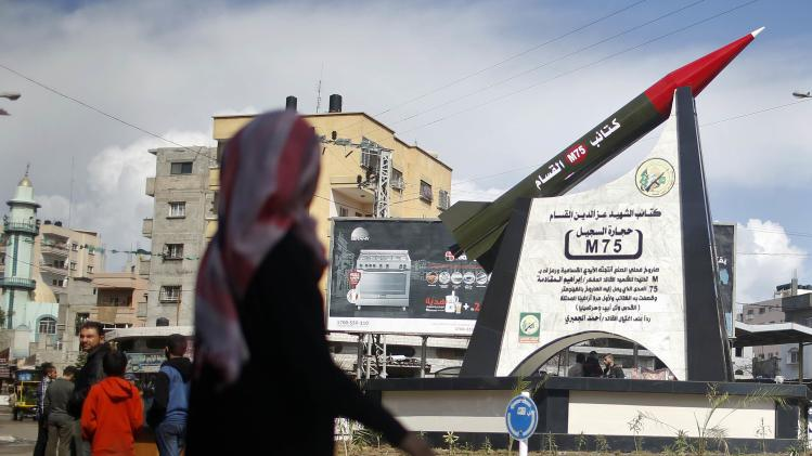 Palestinian girl walks past a monument of a homemade M75 rocket in the middle of a square in Gaza City
