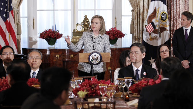Secretary of State Hillary Rodham Clinton, left, gives remarks with Treasury Secretary Timothy Geithner, right, during a dinner for the joint meeting of the U.S.-China Strategic and Economic Dialogue at the State Department Monday, May 9, 2011 in Washington. (AP Photo/Alex Brandon)