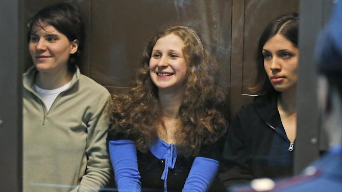 RETRANSMISSION FOR ALTERNATIVE CROP - Feminist punk group Pussy Riot members, from left, Yekaterina Samutsevich, Maria Alekhina, centre, and Nadezhda Tolokonnikova sit in a glass cage at a court room in Moscow, Wednesday. Oct. 10, 2012. Moscow appeals court freed Yekaterina Samutsevich of jailed band Pussy Riot but upheld a prison sentence for Nadezhda Tolokonnikova and Maria Alekhina. The judge ruled that Yekaterina Samutsevich's sentence should be suspended because she was thrown out of the cathedral by guards before she could take part in the performance. (AP Photo/Sergey Ponomarev)