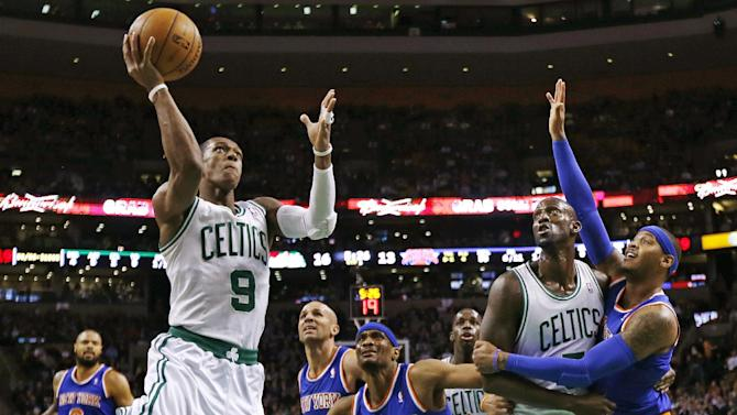 Boston Celtics guard Rajon Rondo (9) drives to the basket as Kevin Garnett blocks out New York Knicks forward Carmelo Anthony, right, during the first quarter of an NBA basketball game in Boston, Thursday, Jan. 24, 2013. (AP Photo/Charles Krupa)