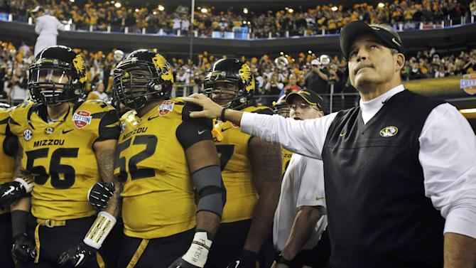 In this Jan. 3, 2014 file photo, Missouri head coach Gary Pinkel, right, and players, including offensive linesman Robert Luce (56) and defensive lineman Michael Sam (52), prepare to take the field for the Cotton Bowl NCAA college football game against Oklahoma State, in Arlington, Texas.  Michael Sam hopes his ability is all that matters, not his sexual orientation.  Missouri's All-America defensive end came out to the entire country Sunday night, Feb. 9, 2014, and could become the first openly gay player in America's most popular sport