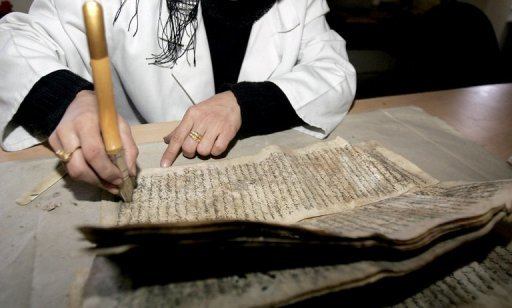 An Iraqi specialist repairs damaged manuscripts at the Iraqi National Library and Archives in Baghdad. The terror of Saddam Hussein's secret police has lived on long after his fall through their millions of reports, which are still dragged up by Iraqi politicians and the media, often with damaging results