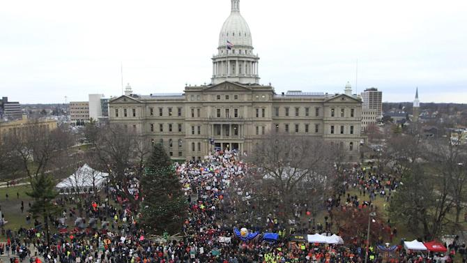 FILE - In this Tuesday, Dec. 11, 2012 file photo, thousands demonstrate at the State Capitol in Lansing, Mich. against the right-to-work legislation that was passed by the state legislature the previous week. (AP Photo/Carlos Osorio)