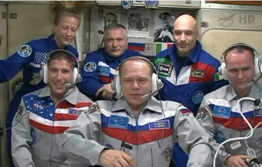 In this image provided by NASA-TV the New Expedition 37 crew members, foreground from left: Mike Hopkins, Sergey Ryazanskiy and Oleg Kotov, were welcomed aboard the International Space Station Thursday Sept. 26, 2013 at 12:34 a.m. EDT. Their Soyuz spacecraft docked to the space station on Wed. at 10:45 p.m. EDT, four orbits after launch at 4:58 p.m. from Kazakhstan. The new residents were greeted by Expedition 37 Commander Fyodor Yurchikhin, rear center and Flight Engineers Karen Nyberg, left, and Luca Parmitano. (AP Photo/NASA)