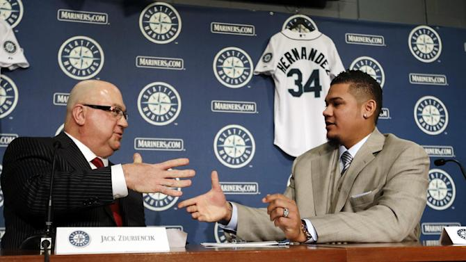 Seattle Mariners' Felix Hernandez, right, shakes hands with general manager Jack Zduriencik after signing a agreement in his new contract to start a news conference, Wednesday, Feb. 13, 2013, in Seattle. Hernandez signed a seven-year contract with the Mariners that makes him the highest-paid pitcher in baseball. The new deal will be worth $175 million. (AP Photo/Elaine Thompson)