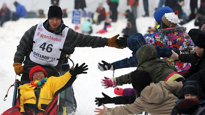 Michael Williams, Jr., greets fans along Cordova Street during the ceremonial start of the Iditarod Trail Sled Dog Race on Saturday, March 2, 2013, in Anchorage, Alaska. The competitive portion of the 1,000-mile race is scheduled to begin Sunday in Willow, Alaska. (AP Photo/Anchorage Daily News, Bill Roth)