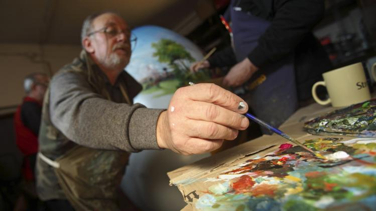 A local artist mixes paint colours before working on completing a two-metre-high Easter egg in the traditional naive art style in Koprivnica
